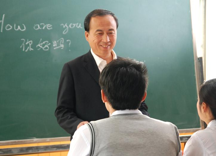 Chinesischkurs in einer kleinen Gruppe. Der Lehrer steht vor den Teilnehmenden und hört diesen lächelnd zu.