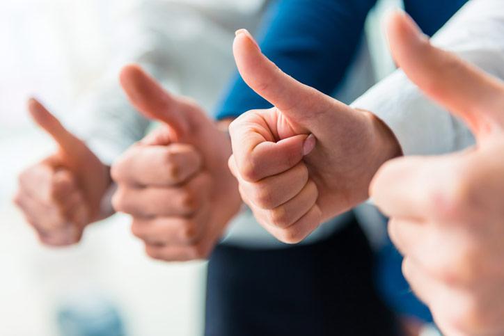 Sprachkurse für Firmen bei der Sprachschule Schneider. Eine Gruppe von Firmenmitarbeitern hebt die Daumen hoch