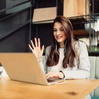 Eine junge Frau lernt Deutsch online via Videokonferenz und winkt ihrer Lehrperson zu.