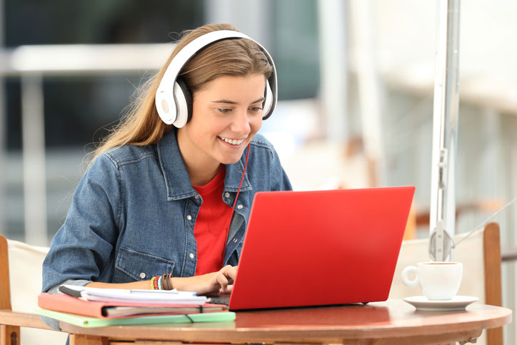 Eine junge glückliche Frau mit Kopfhörer lernt Englisch online per e-Learning auf ihrem Laptop.