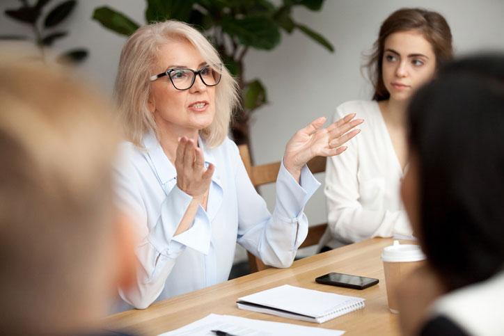 Englischkurs in einer Firma. Die Lehrerin spricht zu den Kursteilnehmenden, die um einen Tisch herum sitzen.