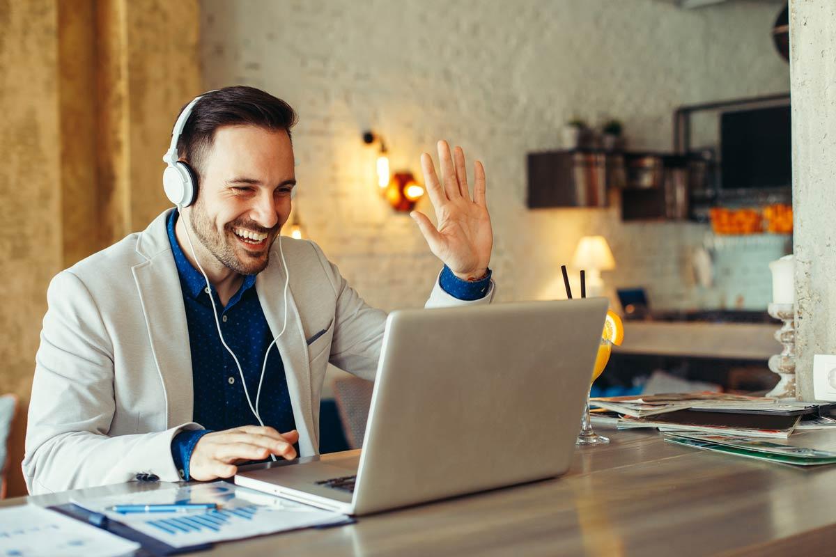 Ein Mann lernt Englisch online via Videokonferenz und winkt seiner Lehrperson zu.