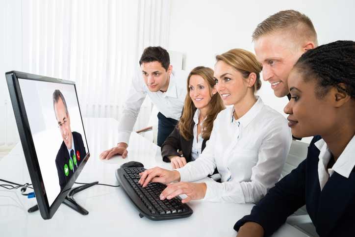 Eine kleine Gruppe Mitarbeiter einer Firma lernt Französisch per Videokonferenz im online Gruppenkurs
