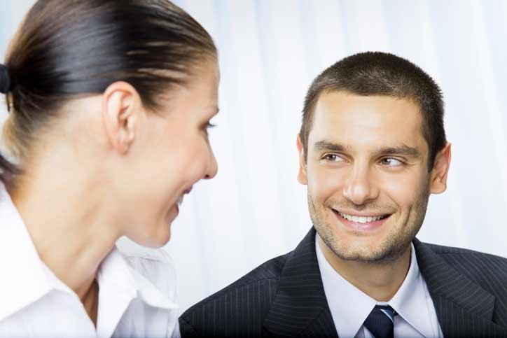 Französischkurs im Privatunterricht. Lehrer und Schülerin in Business Outfit lachen sich an.