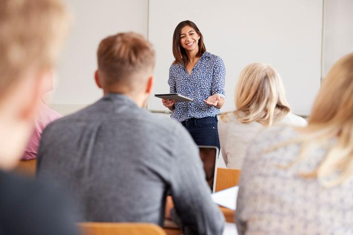 Italienischkurs in einer kleinen Gruppe. Die Lehrperson erklärt am Flipchart, den Italienisch lernenden zugewandt. - Fotograf > getty images