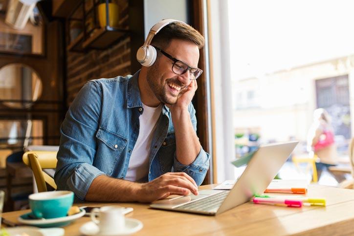 Ein Mann lernt Italienisch online und spricht mit seiner Lehrperson via Video Chat an seinem Laptop - Fotograf > getty images