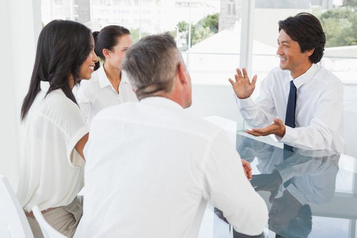 Japanisch lernen in einer Firma. Der japanische Lehrer sitzt am Tisch gegenüber den Teilnenehmenden.