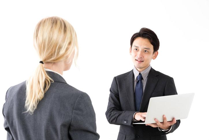 Japanischhkurs im Immersionsunterricht. Der Lehrer steht vor der Teilnehmerin und hält ein Laptop in der Hand.