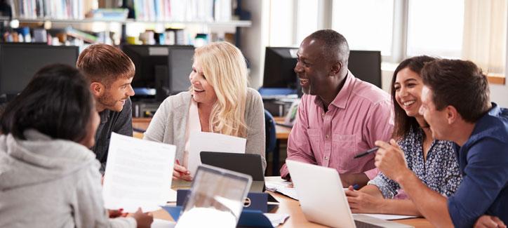 Russischkurs in einer Firma. Die Lehrerin und die Teilenehmenden sitzen um einen Tisch herum.
