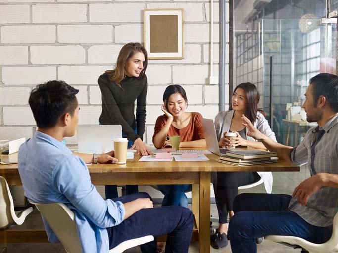 Schweizerdeutsch lernen in einer Firma. Die Lehrerin steht bei den Teilenehmenden, die um einen Tisch herum sitzen.