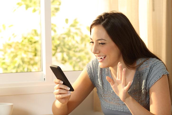 Eine junge Frau begrüsst ihre online Lehrperson auf dem Handy