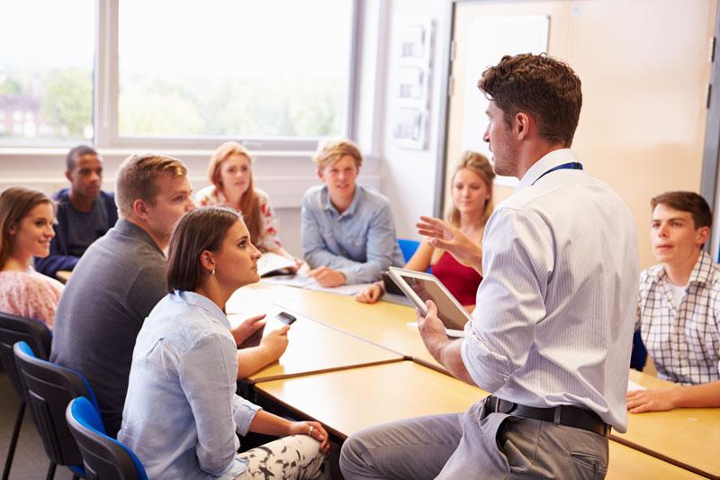 Deutsch lernen im Deutsch Intensivkurs in einer kleinen Gruppe an der Sprachschule Schneider in Zürich. Der Lehrer steht, die Schüler sitzen um den Tisch herum.