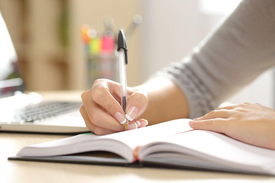 Jugendiche schreibt einen Aufsatz in ein Heft während eines Aufsatzkurses.