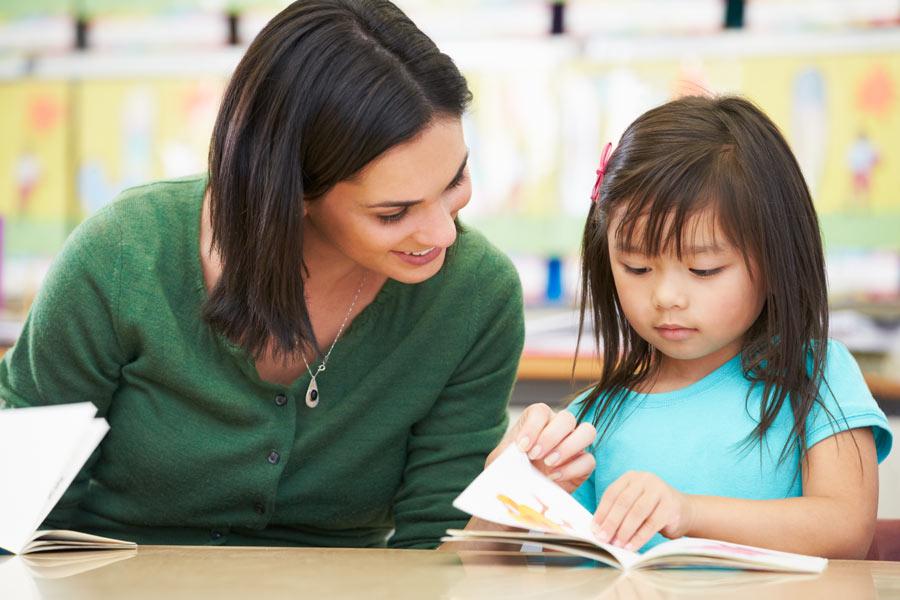 Lehrperson lernt mit Kind im Einzelunterricht auf Deutsch zu lesen