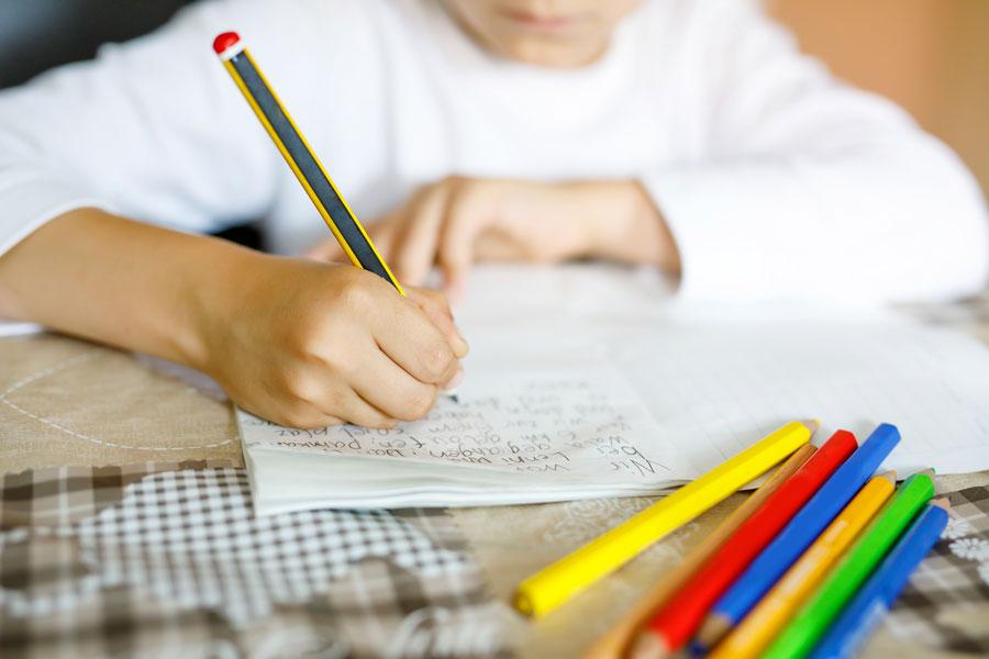 Kind schreibt im Förderunterricht in ein Heft.
