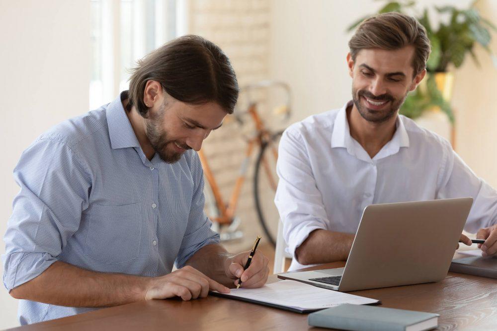 Mann unterschreibt seinen Arbeitsvertrag