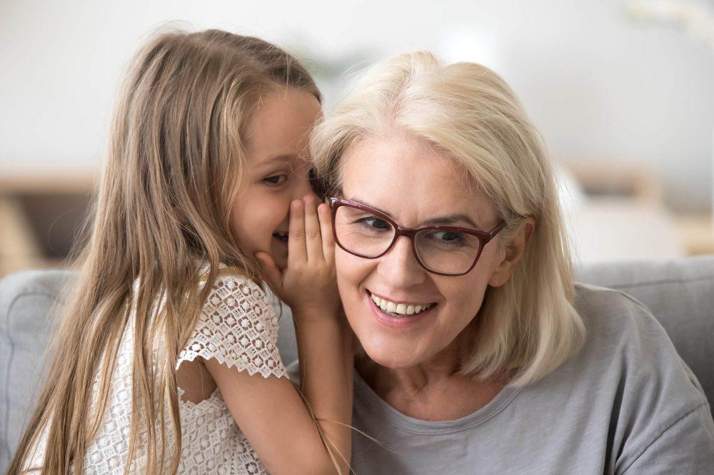 Mädchen flüstert ihrer Oma etwas zu