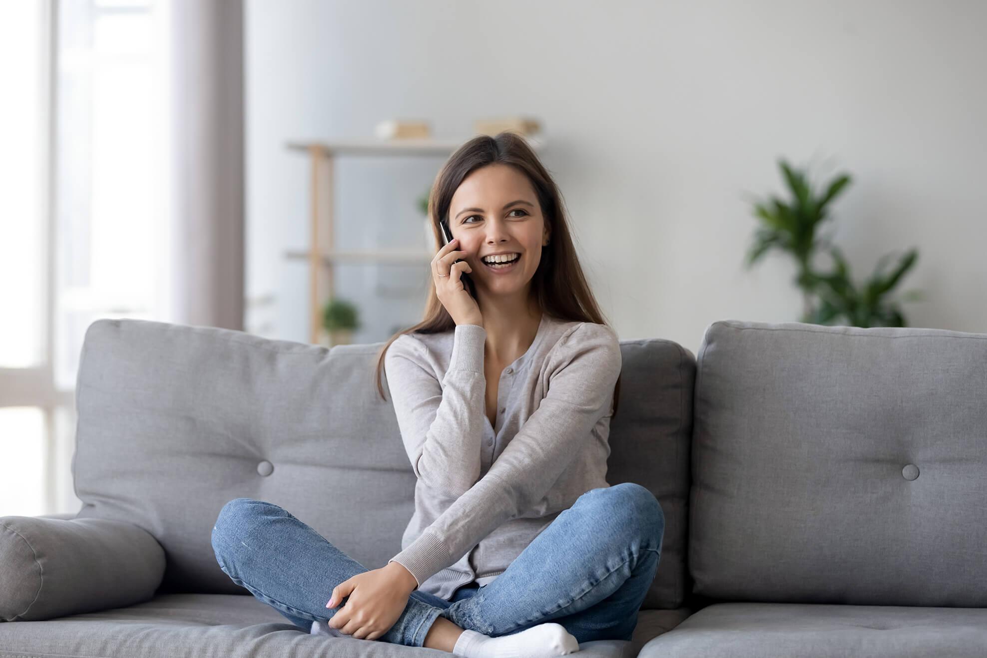 Frau telefoniert auf der Couch
