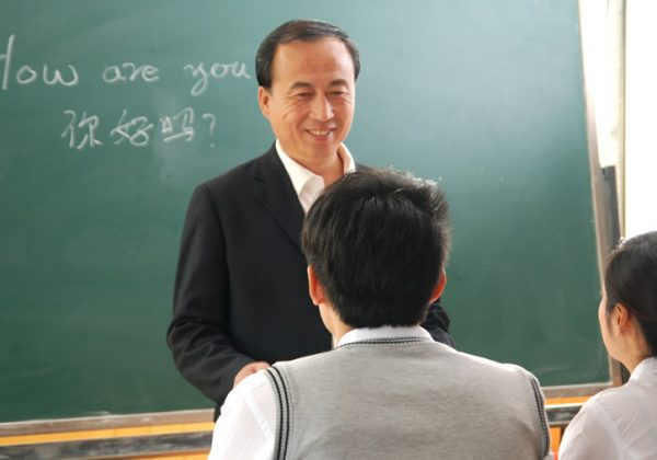 A Chinese course in a small group. The teacher is standing in front of the students and is listening to them and smiling at them.