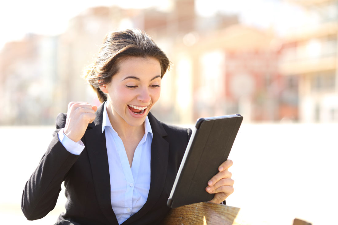 A business executive woman in an online video chat with her English teacher making a winner sign with her hand.