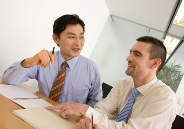 An employee is learning Japanese in a customised 121 language course in he's company and is sitting next to the teacher at the table.
